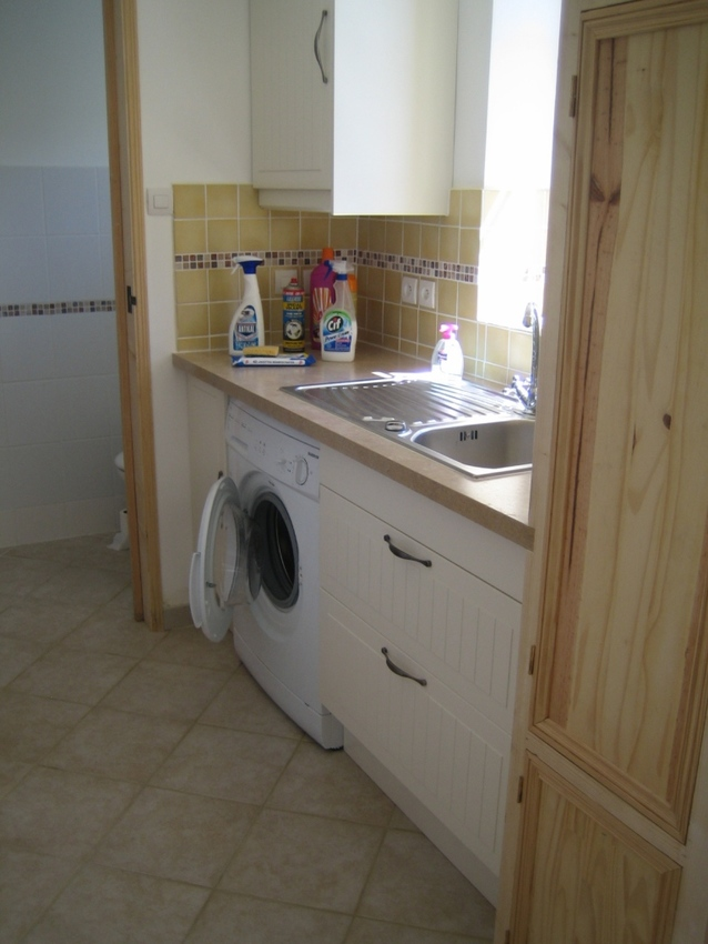 Large utility room with toilet beyond